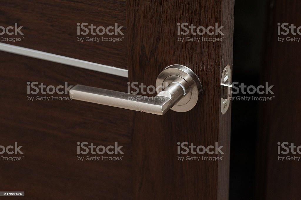 Modern metal door handle in living room stock photo