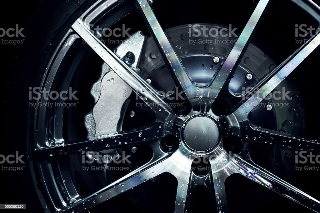 Modern metal rims on car at dark stock photo