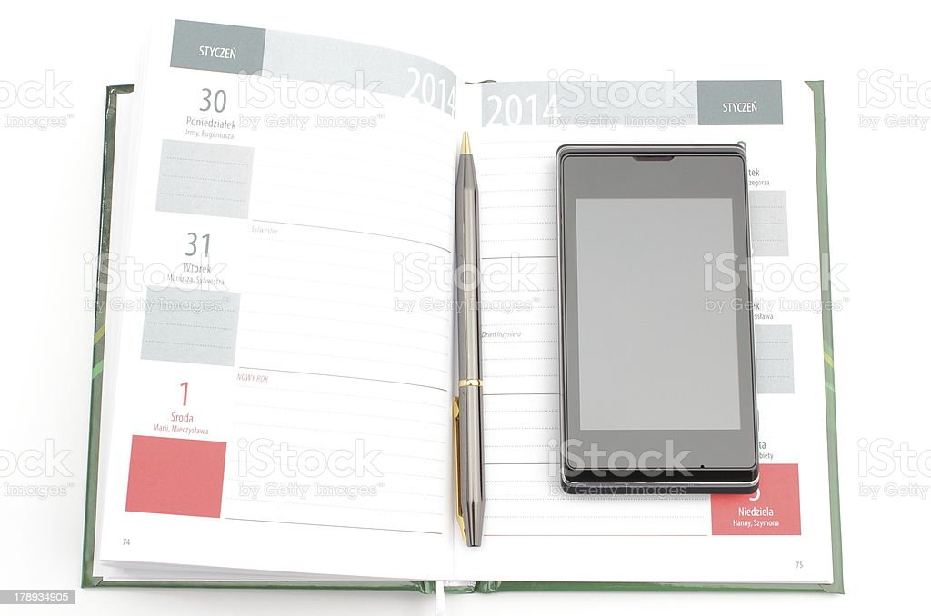 Modern mobile phone and pen lying on open calendar royalty-free stock photo