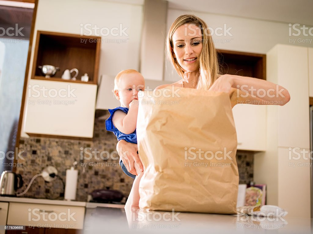 Modern Mom Unpacking Groceries with Infant Girl In Arms stock photo
