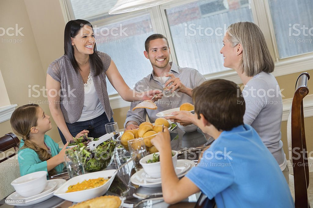 Modern mother serving dinner to her three generation family royalty-free stock photo