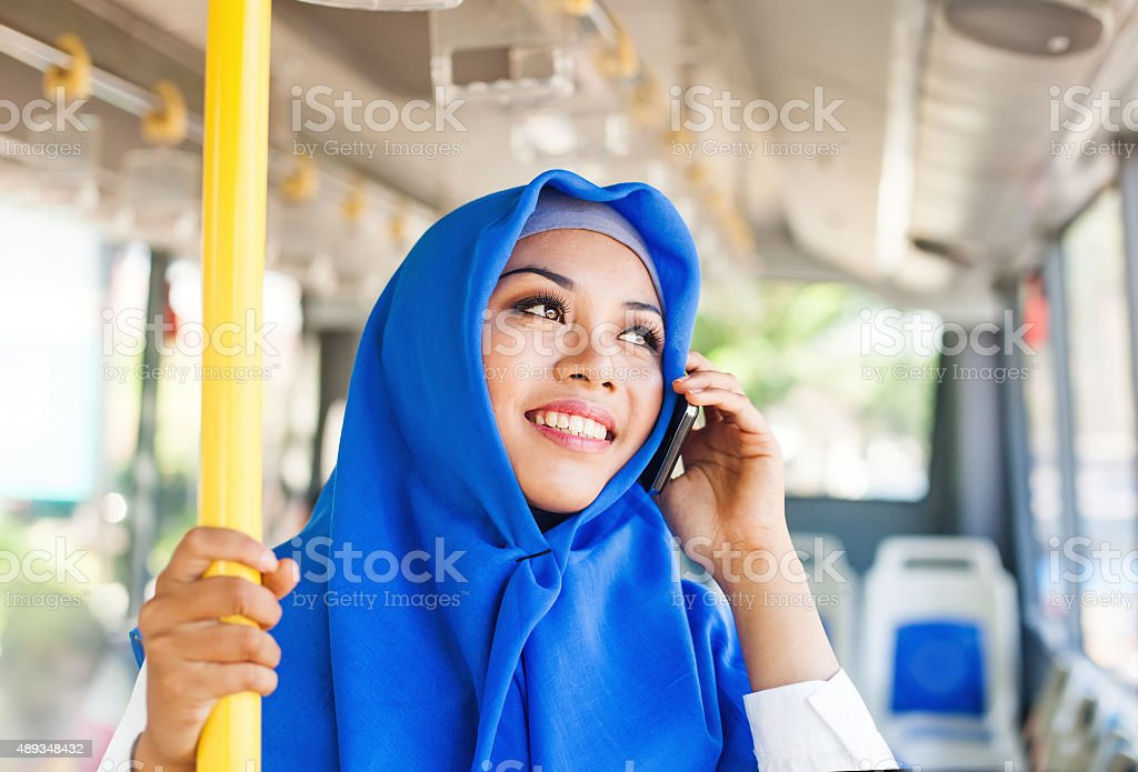 Modern muslim woman in a bus talking on mobile phone stock photo