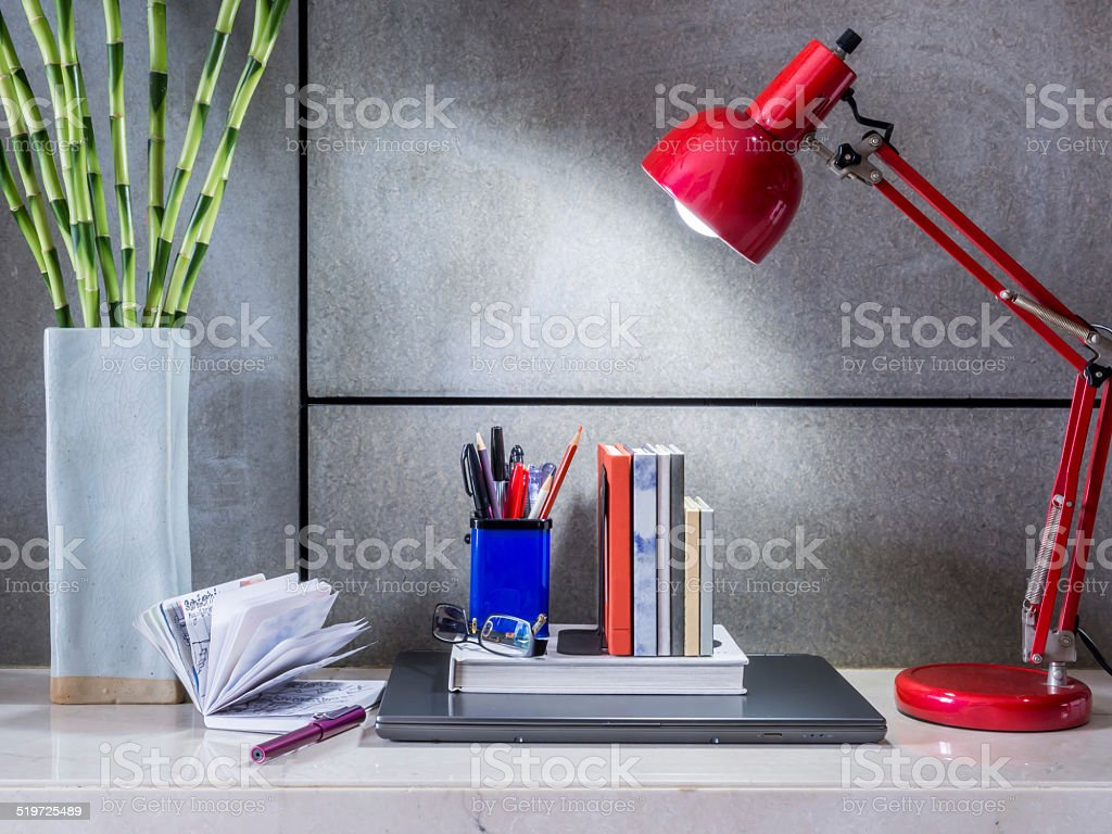 Modern office desk with laptop, lamp and vase of flowers stock photo