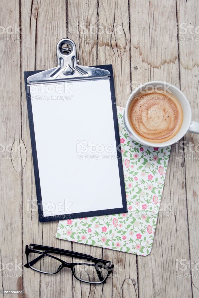 office desk with notepad and cup of coffee