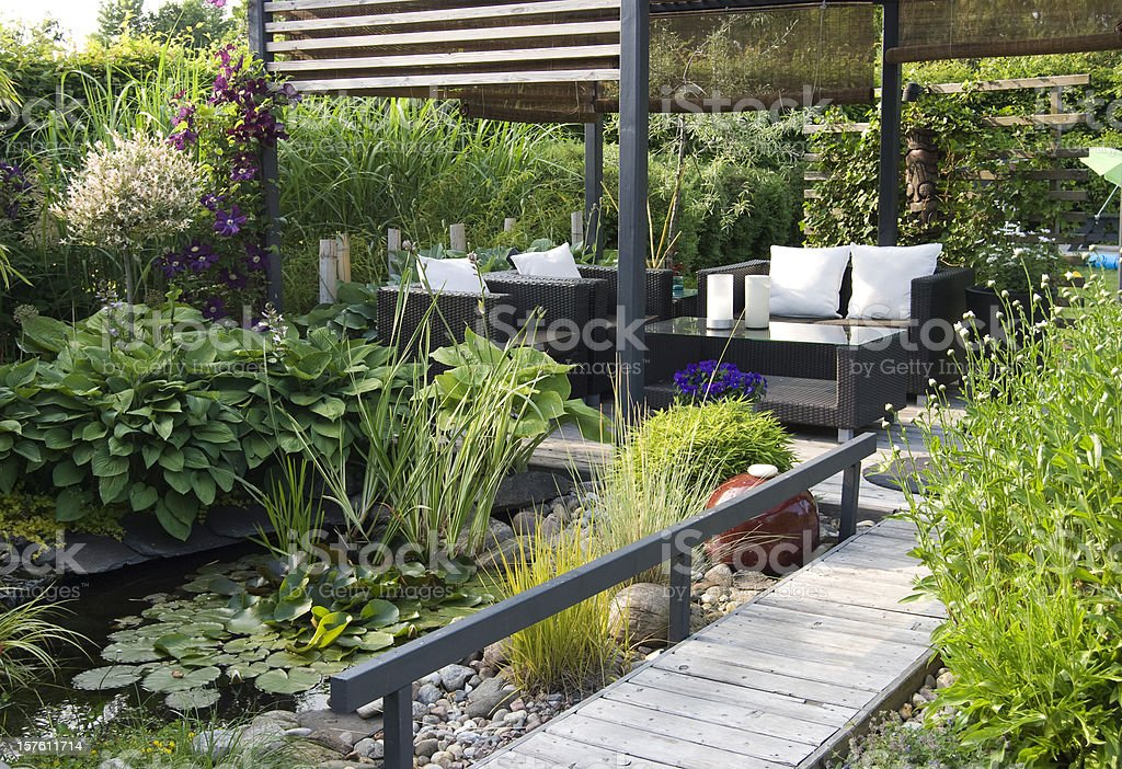 Modern patio garden lounge with a pond and outdoor sofas stock photo