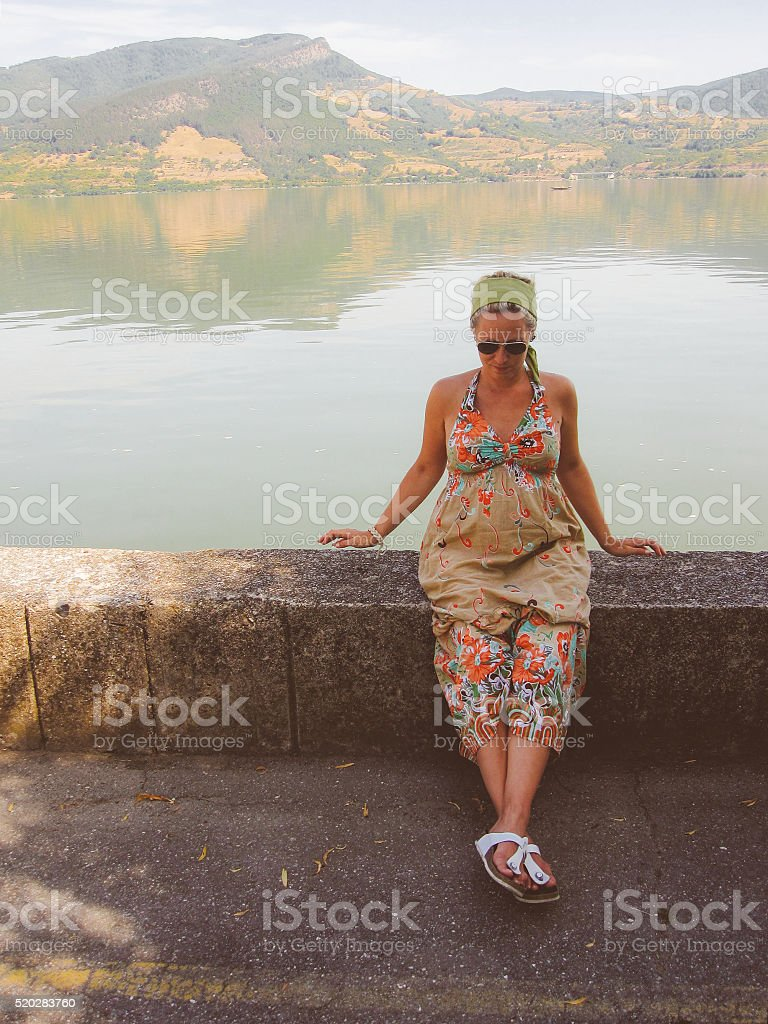 Modern pregnant woman sitting on a riverbank stock photo