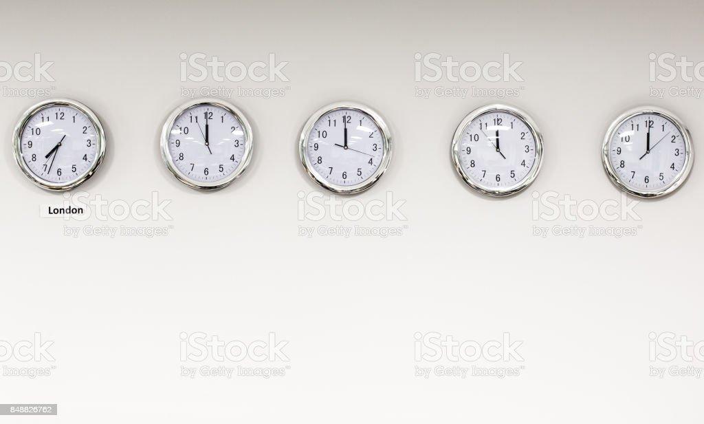 Modern quarz analog clocks on white wall in office stock photo