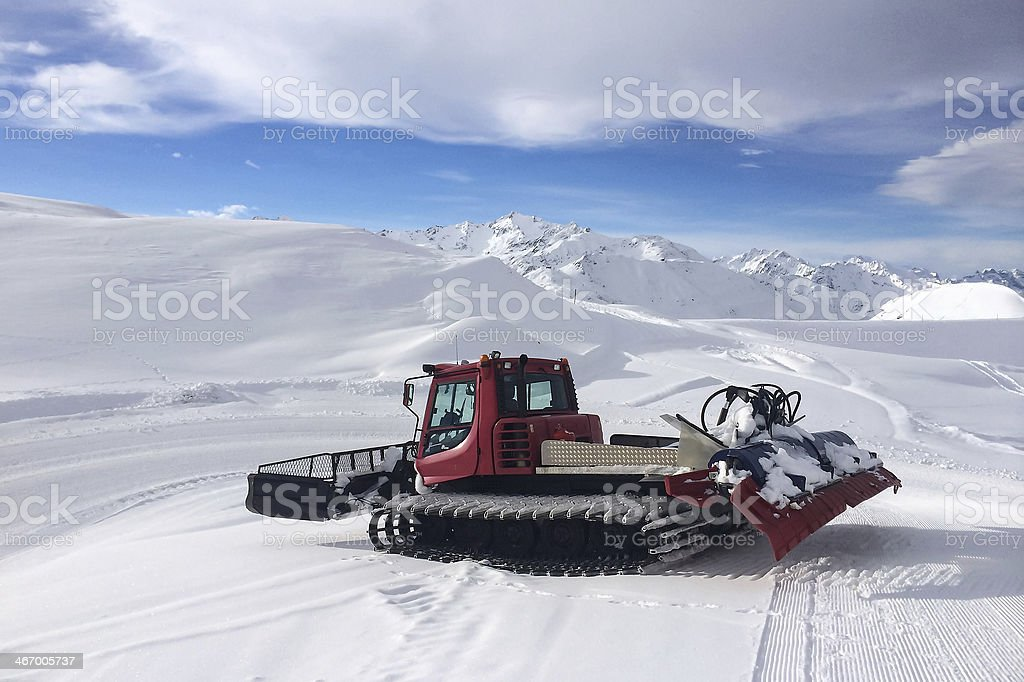 Modern red snow groomer in a sunny day stock photo