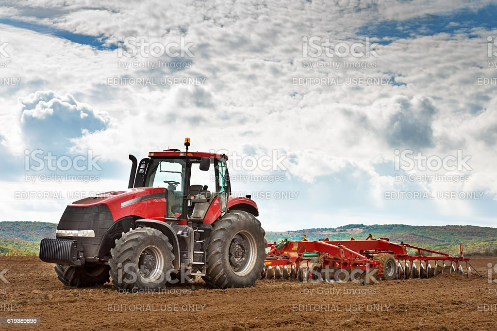 modern red tractor in the agricultural field. stock photo