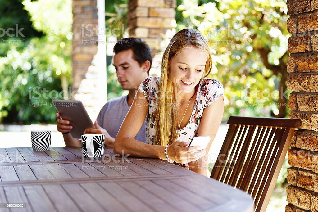 Modern relationship: young couple keeping in touch via social media stock photo