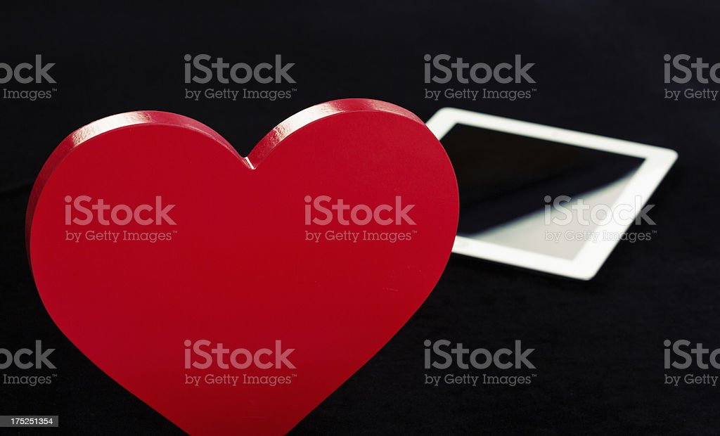 Modern romance: red heart and digital tablet on black royalty-free stock photo