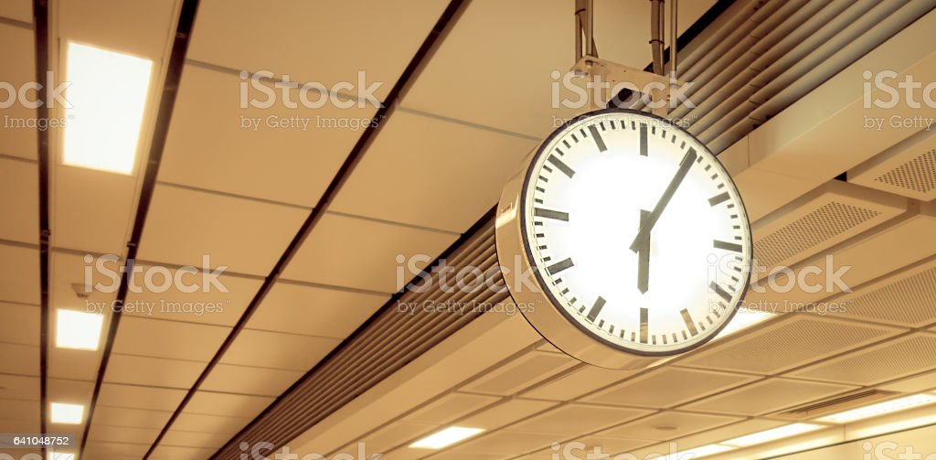 Modern round ceiling clock in hallway copy space stock photo