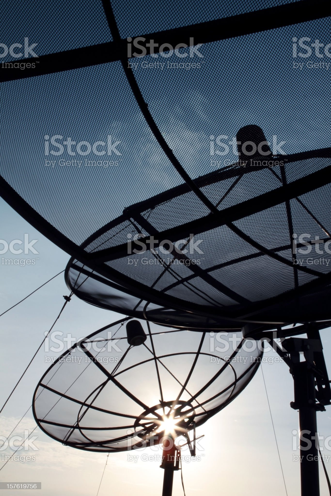 Modern satellite dish at dusk with sunlight flare royalty-free stock photo