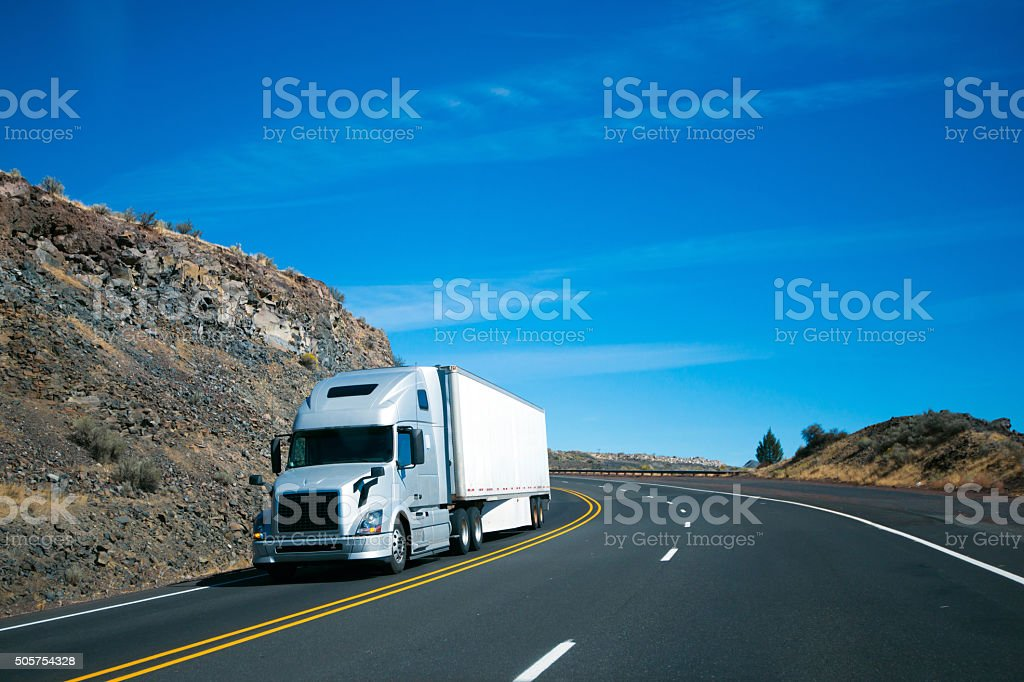 Modern semi truck and trailer on turning rocky windy road stock photo
