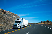 Modern semi truck and trailer on turning rocky windy road