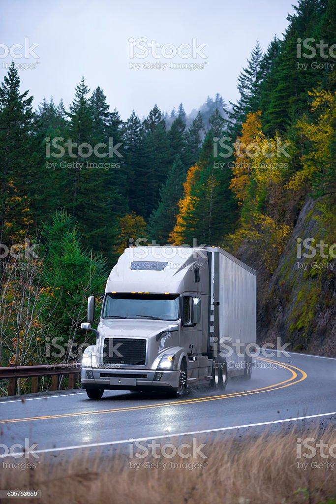 Modern semi truck trailer in rain autumn winding road stock photo