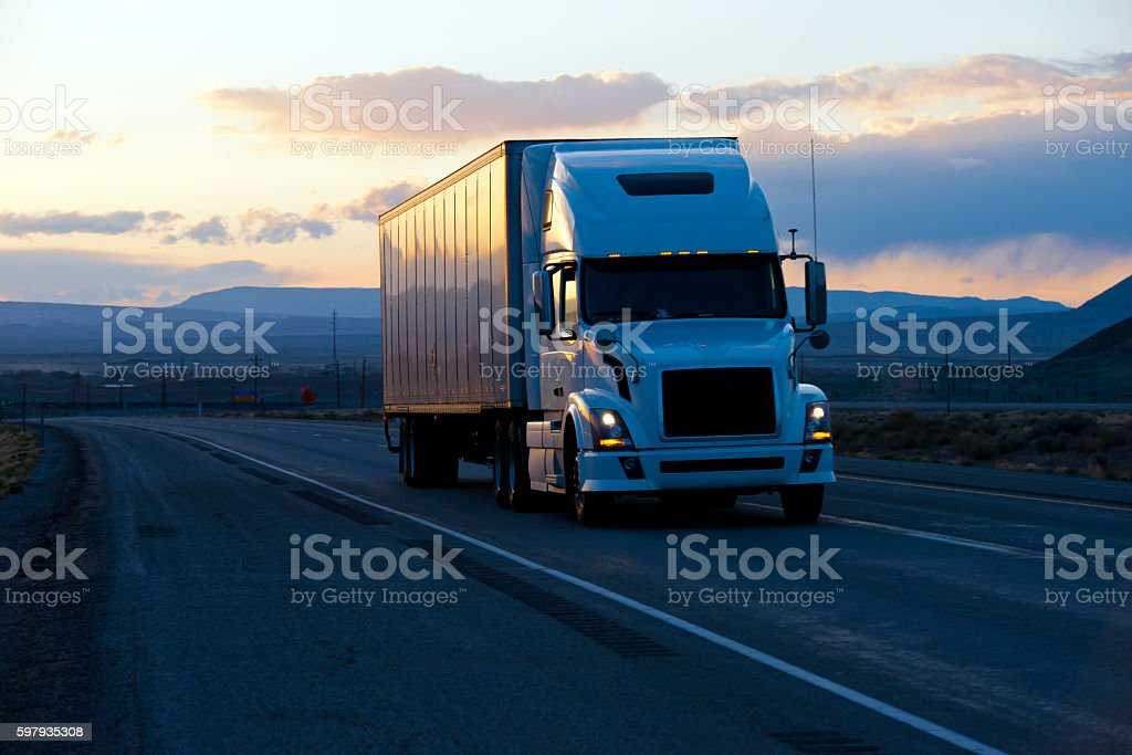 Modern semi truck trailer on twilight highway stock photo