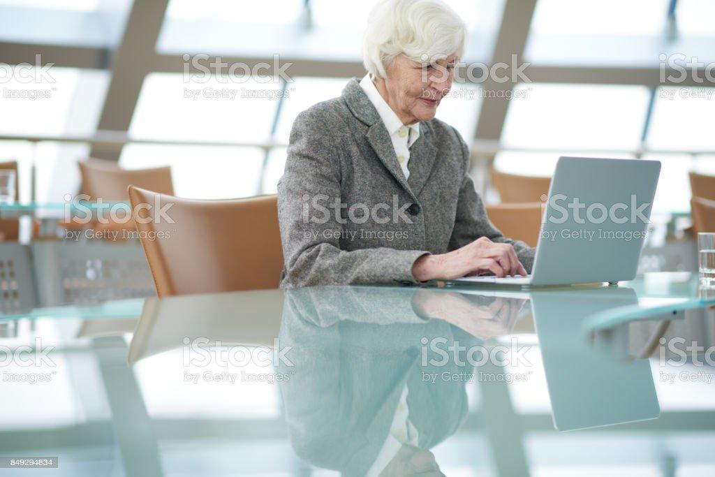 Modern senior businesswoman using laptop stock photo