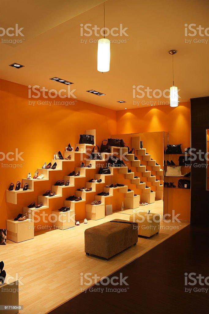 Modern shoe store with orange walls at night royalty-free stock photo