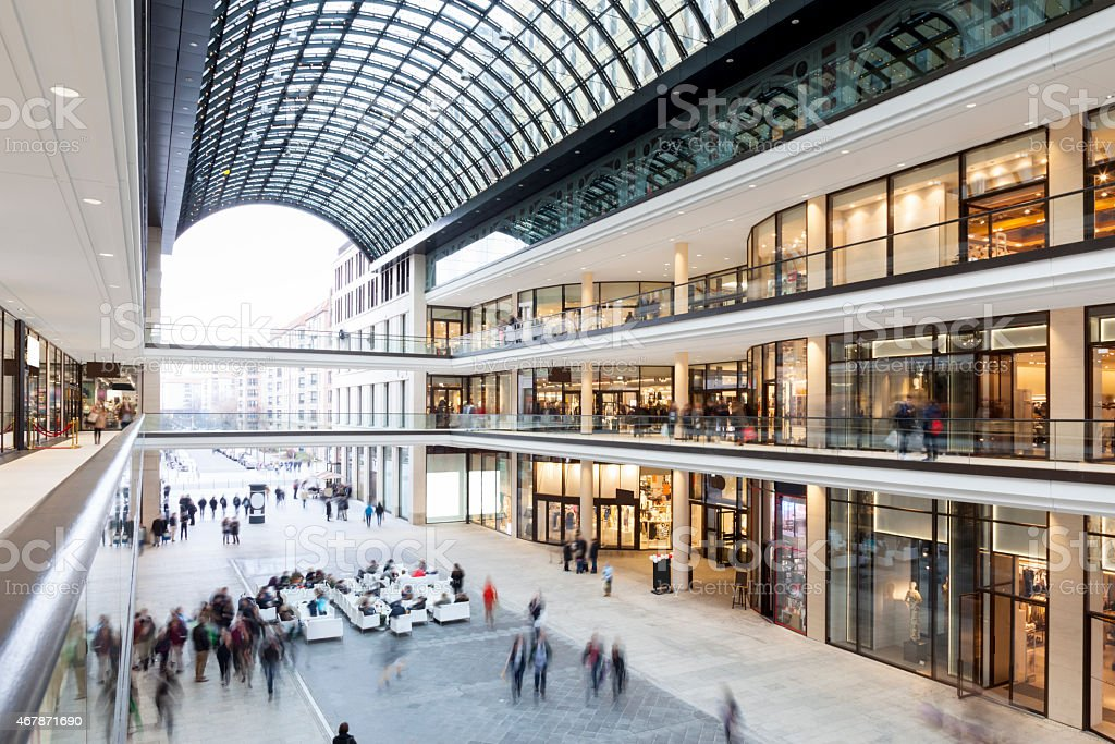 Modern Shopping Mall with stores, Cafe and Shoppers Walking Around stock photo