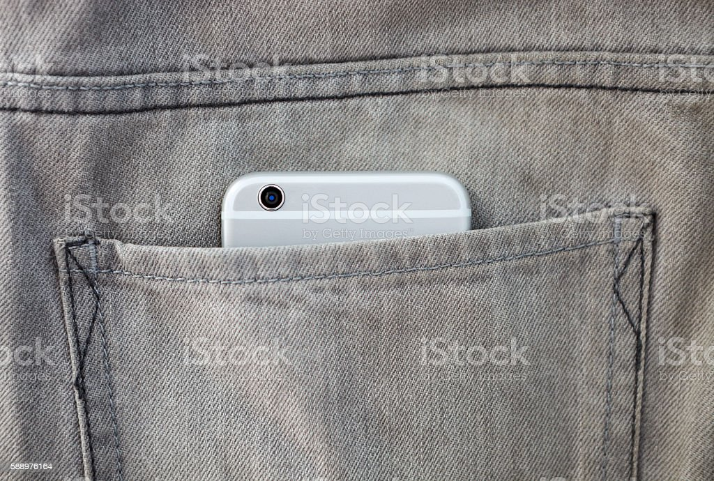 Modern smartphone in jeans pocket stock photo