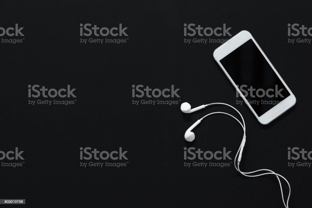 modern smartphone with blank screen and earphones isolated on black stock photo