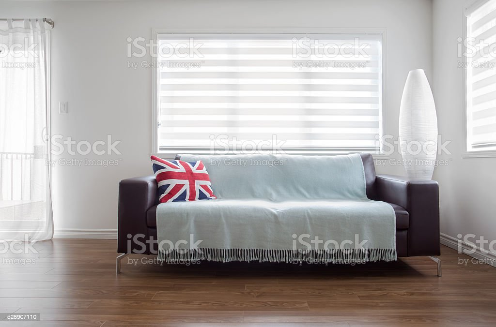 Modern Sofa in bright living room with zebra blinds. stock photo