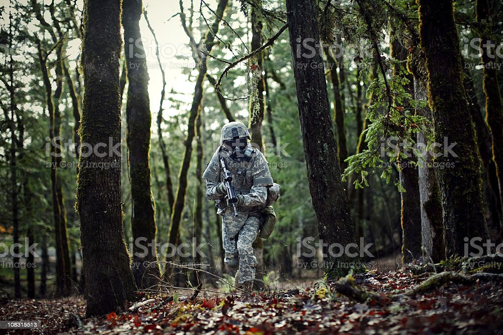Modern Soldier in Dark Woods with Gun royalty-free stock photo