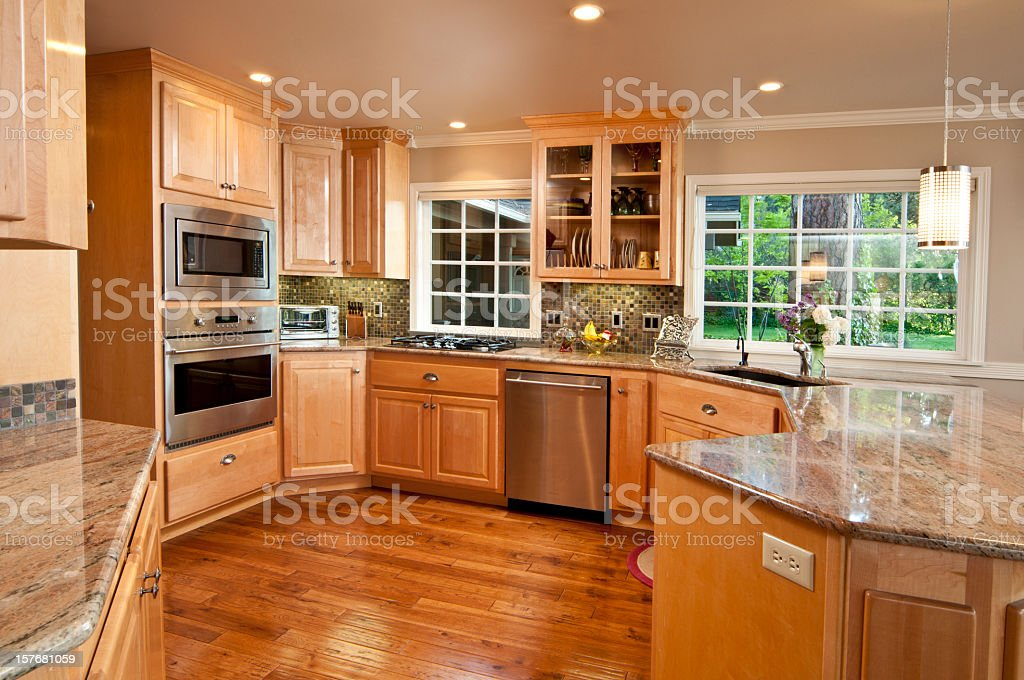 Modern, spacious kitchen with hardwood floors and cabinets stock photo