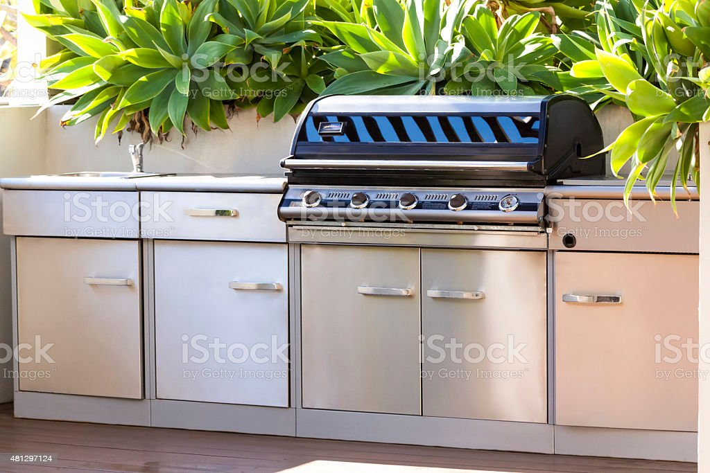 Modern stainless steel barbecue grill with staineless steel cupboards stock photo