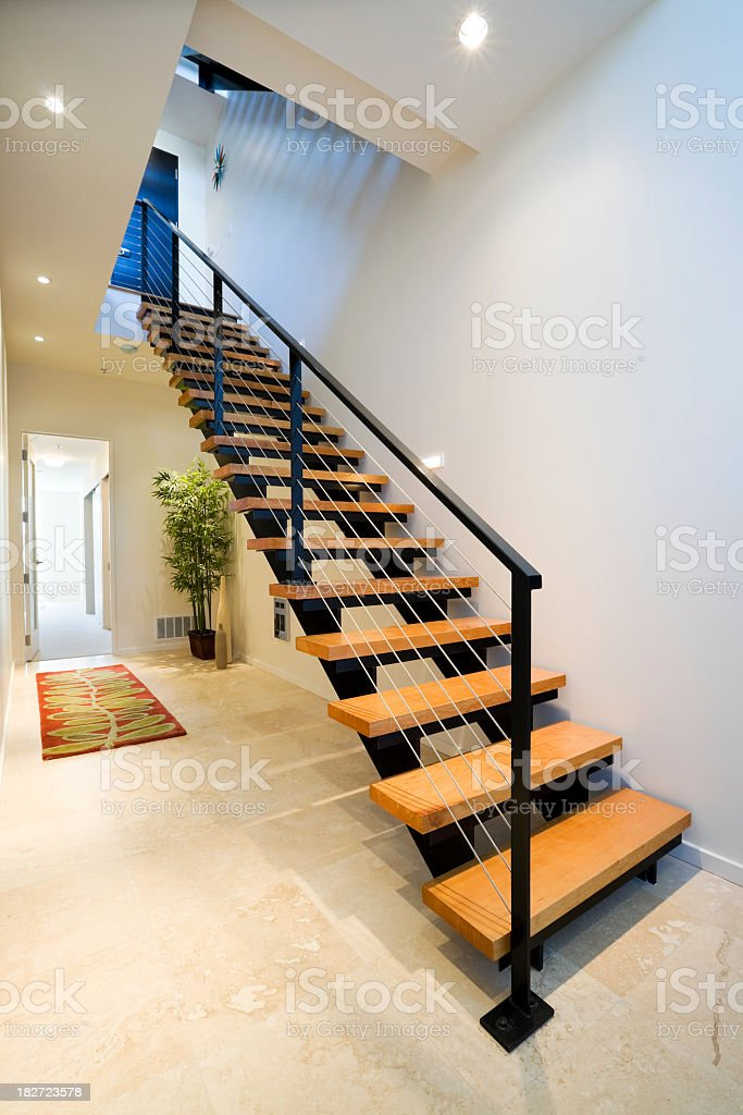 A modern stair with open wooden treads and metal handrail royalty-free stock photo