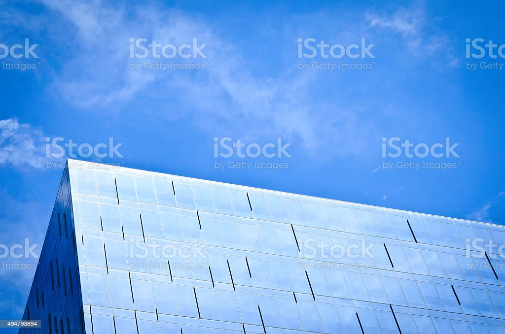 Modern steel and glass building with sky reflecting in the glass royalty-free stock photo