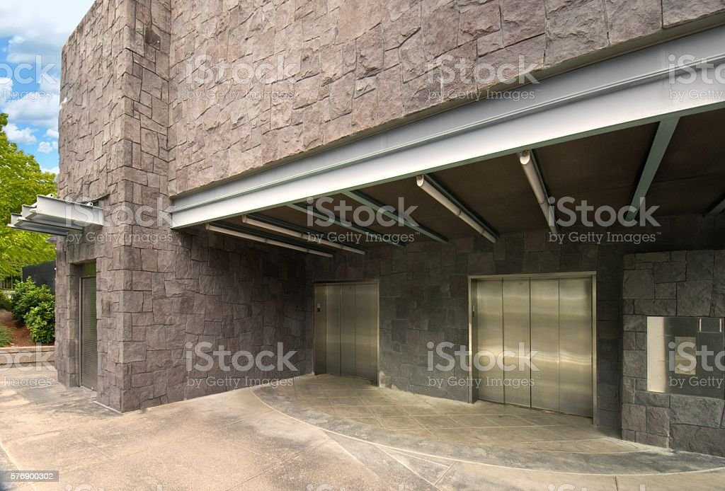 Modern Stone Building Façade, Cantilevered Roofs, Steel Elevator Doors, 3XL stock photo