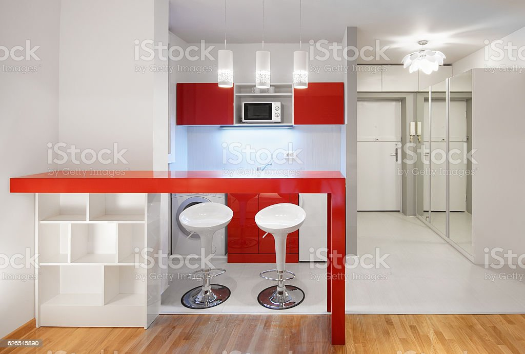 Modern studio flat or hotel kitchen in red stock photo