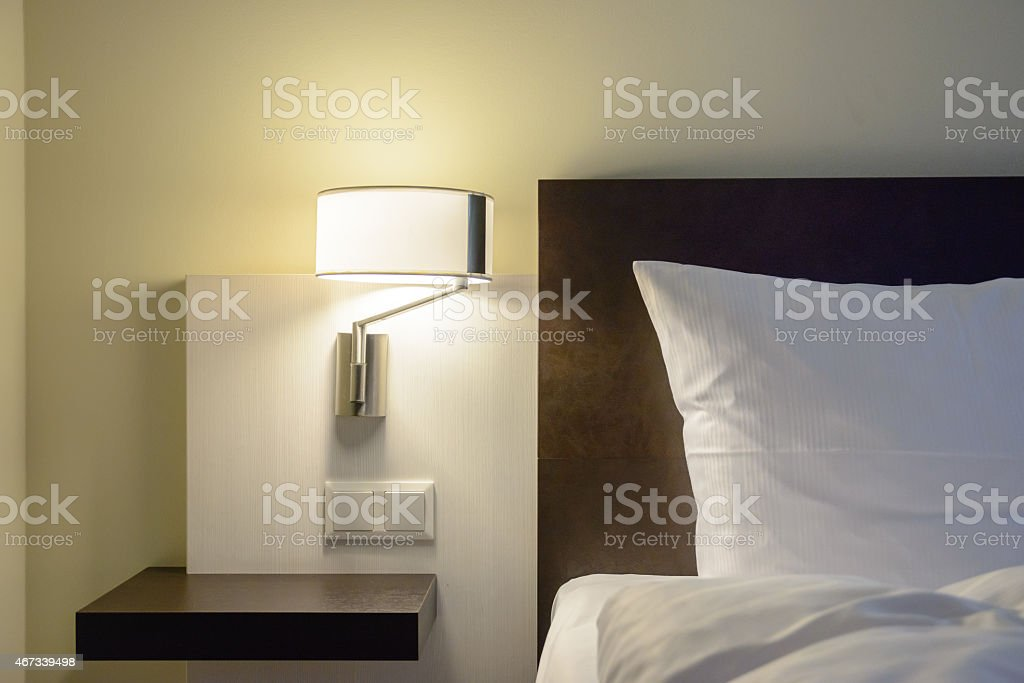 A modern style bedroom featuring a wall lamp stock photo