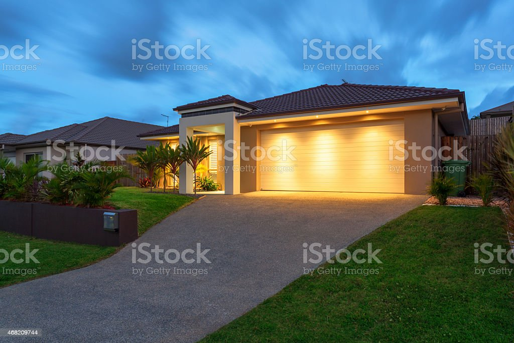 Modern suburban home with lights on at dusk stock photo