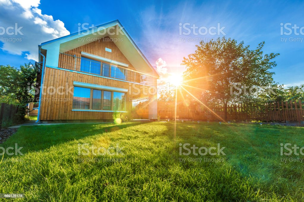 Modern summer cottage against a blue sky in the summer garden stock photo
