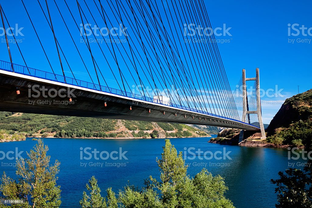 modern suspension bridge across river Luna and reservoir Luna stock photo