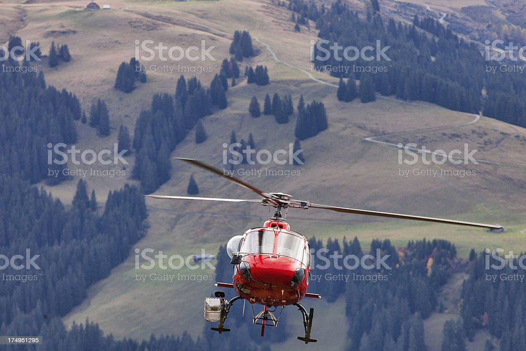 Modern Swiss helicopter air borne with passengers, copy space royalty-free stock photo