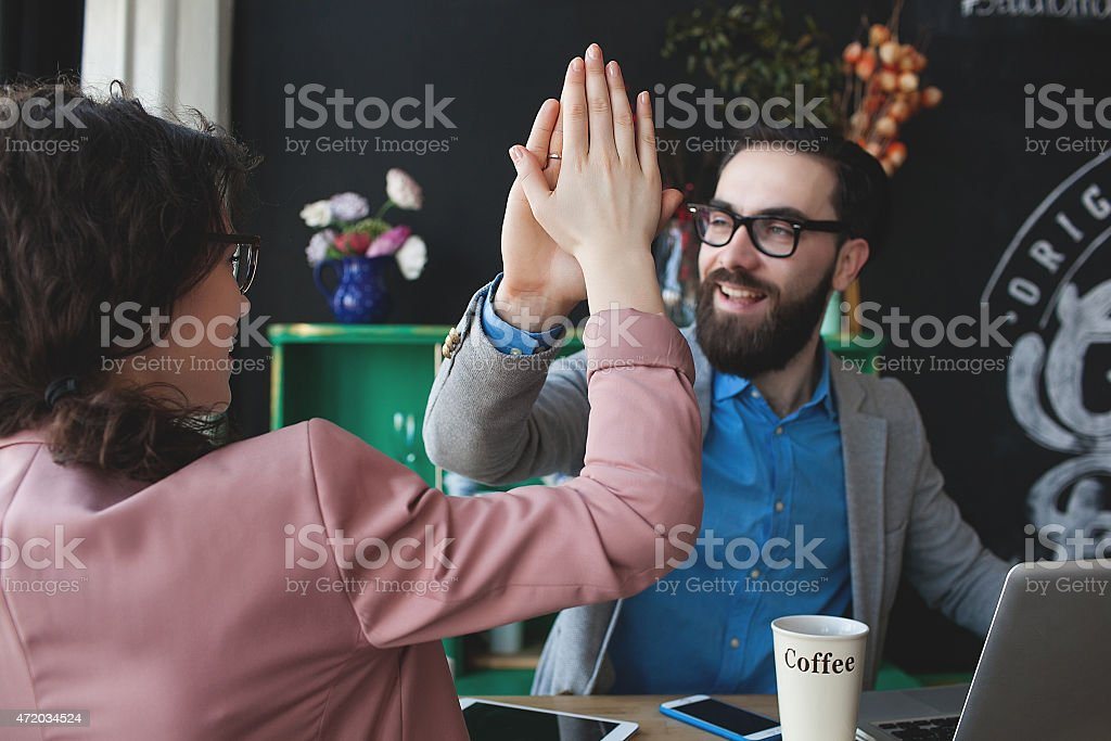 Modern team celebrating success giving five with laptop stock photo