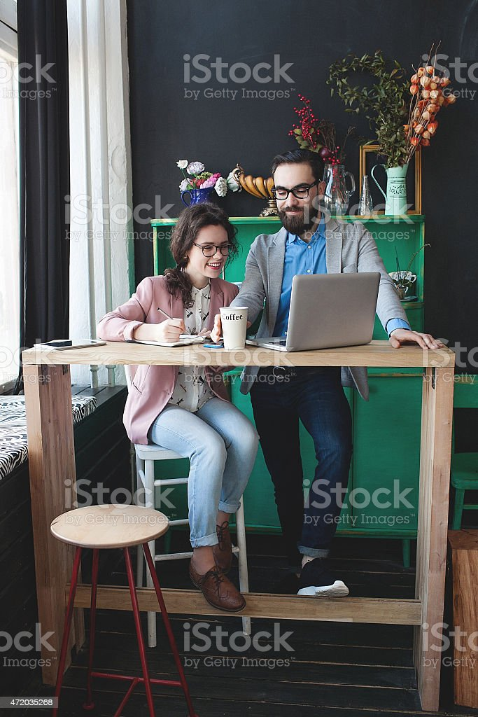 Modern team working in cafe with laptop, smartphone with coffee stock photo