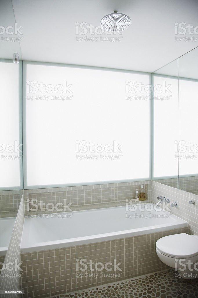 Modern toilet and bathtub in elegant, white bathroom royalty-free stock photo