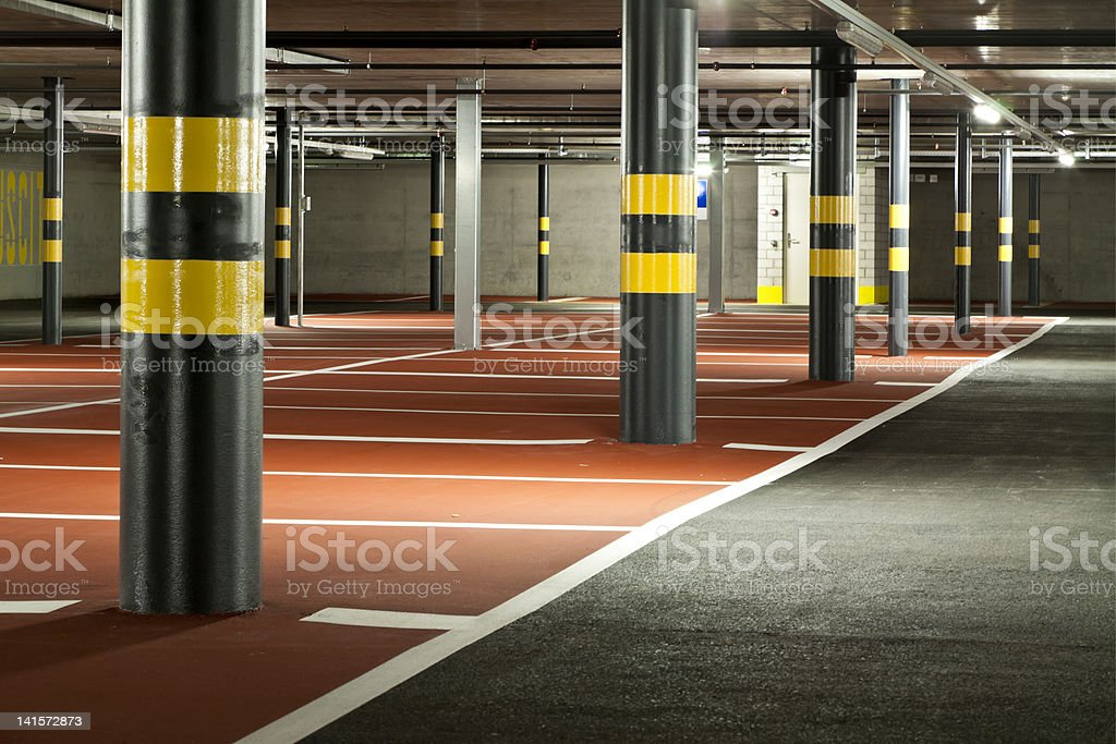 Modern, underground parking lot with pillars and red parking royalty-free stock photo
