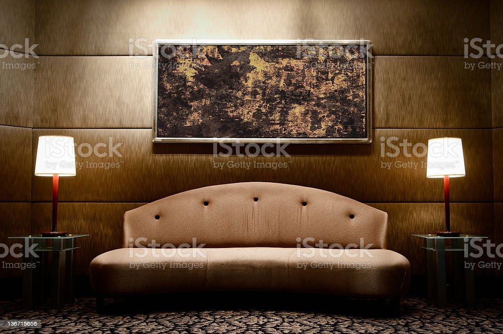 Modern upholstered sofa, flanked by matching lamps and art royalty-free stock photo