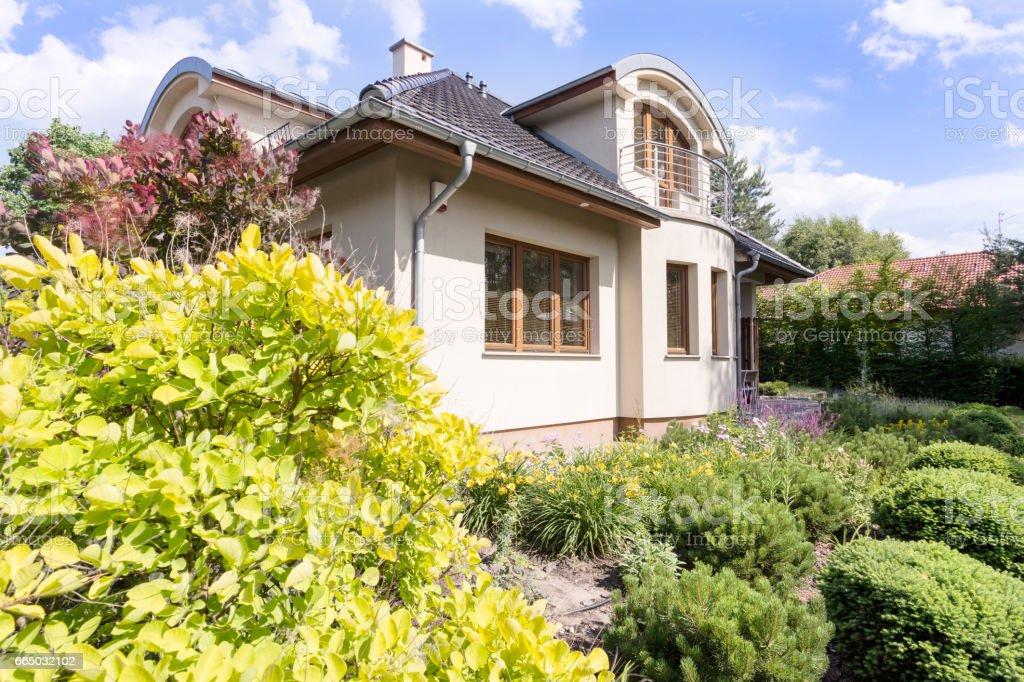Modern villa exterior surrounded by garden stock photo