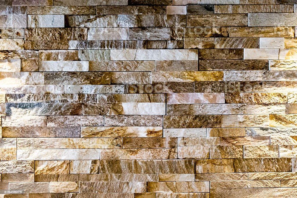 Modern wall lamp on a grungy modern tile / brick natural stone wall stock photo