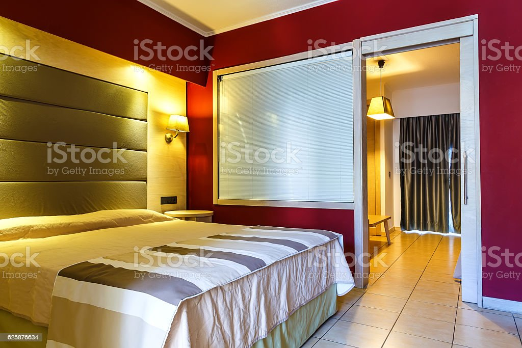 Modern, warm, inviting bedroom or hotel room. Light and shadows stock photo