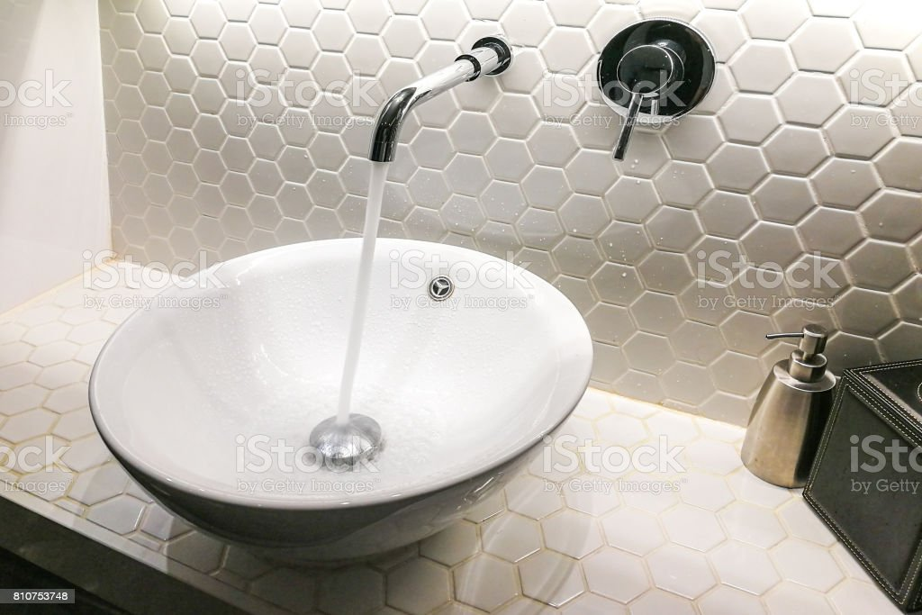 Modern wash basin with running water from tap faucet stock photo