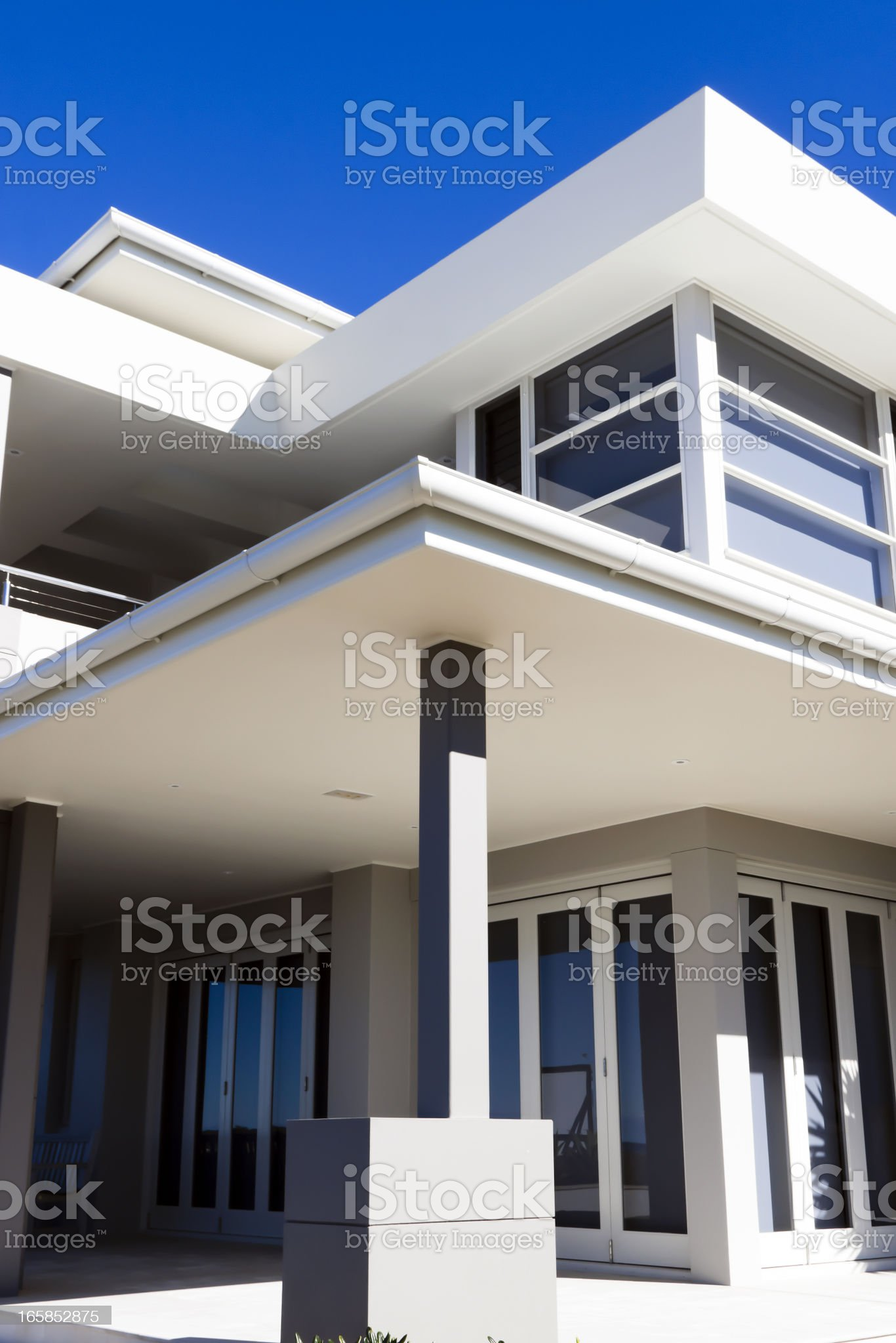 Modern white house in sunlight against blue sky, copy space royalty-free stock photo