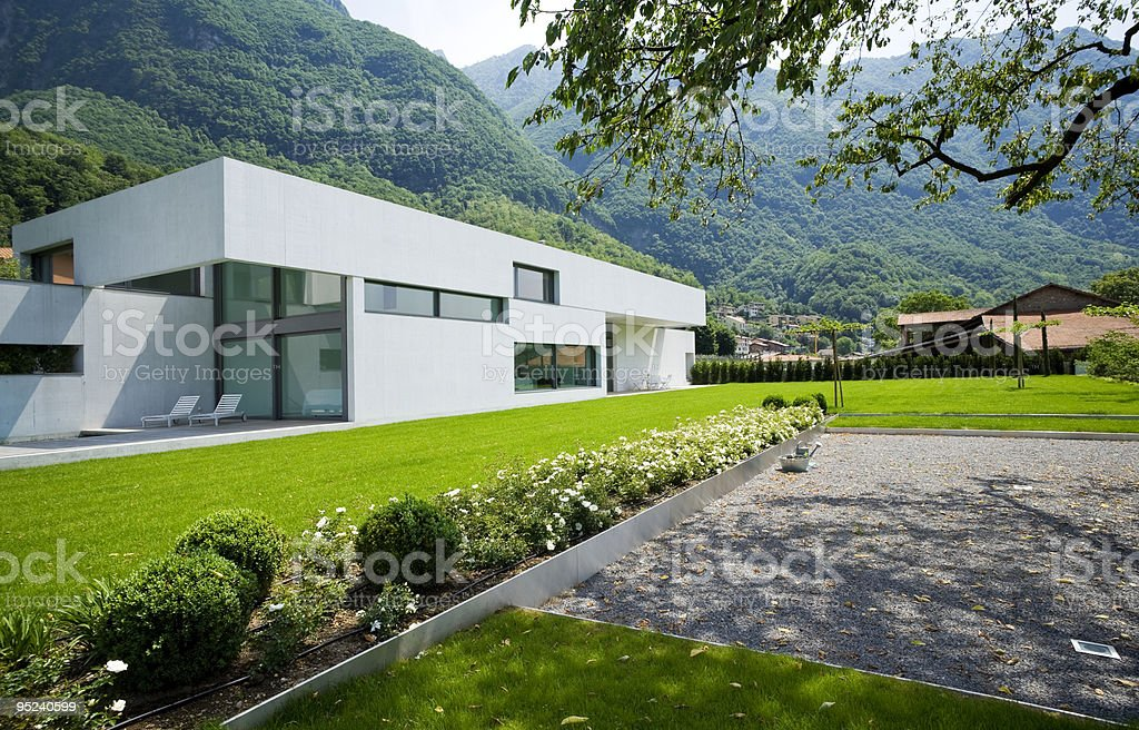 Modern white house with green hills and grass royalty-free stock photo